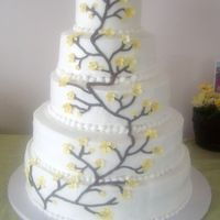Yellow Cherry Blossom  A 5 tier buttercream cake with yellow cherry blossoms to match the wedding colors. 6, 9, 12, 15, and 18 inch tiers. Flowers are gumpaste...