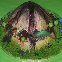 Dinosaur Volcano Buttercream volcano. Airbrushed colors on white buttercream. oreo cookie crumbs spread around. red gel for lava. the dinosaurs are plastic...