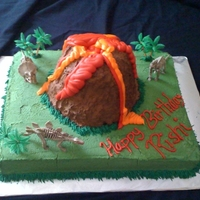 Dinosaur Volcano Cake 1/2 sheet cake with volcano on top made out of cake as well and all covered with whipped topping. Lava is royal icing.