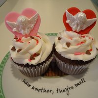 Valentine Cupcakes  Chocolate cupcakes w/ cherry pie filling and topped w/Vanilla buttercream. Fondant decoration hearts and cherubs. For my Grandson's...