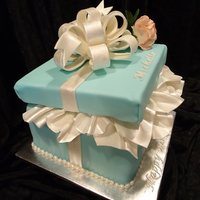Tiffany Gift Box White Almond cake w/Almond Buttercream; covered in fondant. Gumpaste/Fondant bow and tissue. Gumpaste rose. Lid is styrofoam covered in...
