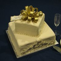 50Th Anniversary Cake This is a 13x13 cake with a 9x9 cake on top. Covered with Fondant with a gold bow. I was quite pleased with it -- it was my second stacked...
