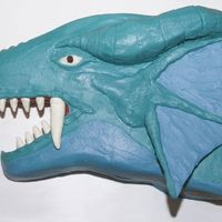 Yu-Gi-Oh's Dragon Timaens Chocolate cake carved to look like the dragon Timaens. Teeth are white chocolate candy clay. Ear is chocolate covered in buttercream. Half...