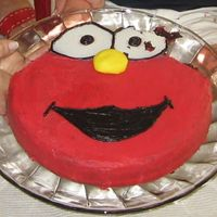 Elmo Cake An Elmo cake using a 10 inch round pan, then cutting out around the outside to make the eyes and decorating the whole thing with icing.