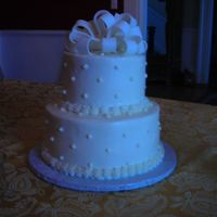 Rainbow Wedding Cake   This cake is rainbow colored sour cream french vanilla with buttercream icing. Swiss dots and a fondant bow finish it off.