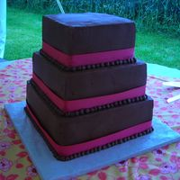 "Chocolate Buttercream   12"", 10"", 8"" square. Chocolate sour cream cake with seedless raspberry filling. Chocolate buttercream with pink ribbon."