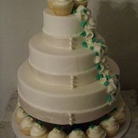 Calla Lily Cupcake Tower Bands of pearlized fondant ribbon are accented by handmade sugar pearls. Miniature calla lilies cascade down the entire piece, and each...
