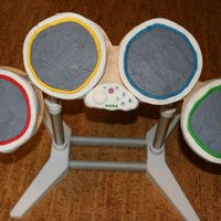 Rock Band Drum Set   4 cake rounds with buttcream frosting and fondant trim. Rice crispie controller with fondant cover/ buttons.