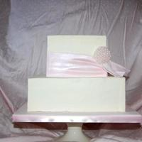 Pink Pearl Bride loved soft, pastel pink. Fondant ribbon with an edible pearl brooch. Melt in your mouth pink champagne cake with smooth champagne...