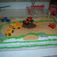 Construction Dirt Cake graham cracker crumbs as dirt, w/grass, pudding mud puddle,rocks, and safety cones for the contruction zone