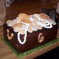 Treasure Chest chocolate cake filled with raspberry and bavarian cream. Chocolate buttercreme frosting. Coins are chocolate. The handles and number 6 are...