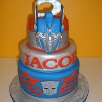 "Optimus Prime!! I made this for my son's 5th B-day. It is all fondant- 10"", 9"" 6"". He wanted a cake with Optimus Prime standing on top..."