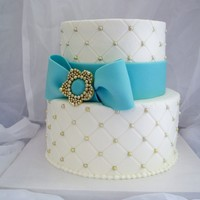 Golden Anniversary Buttercream cake with quilting and gold dragees, fondant ribbon and handmade gumpaste and dragee brooch.