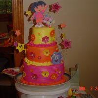 Dora Cake Frosted With Buttercream, Edible Image Plaques, Fondant Flowers, And Gumpaste Stars Dora cake that I made for a litttle girl I take care of. I'm really happy with how it turned out.