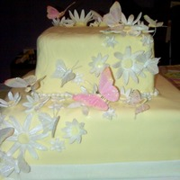 "Butterfly Baby Shower 16"" and 12"" cakes covered in pale yellow Satin Ice fondant, decorated with white gumpaste daisies and silk butterflies."