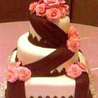 Shenita  Sorry for the grainy photos; done w/ cell phone. For a friend, Fondant covered 6 x 10 rd x 12 sq. golden butter cake w/ creme bouquet...