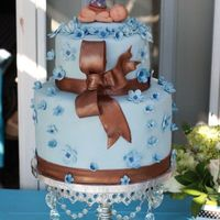 Baby Blue   Covered in fondex with fondex flowers and bow. The baby is marzipan with a fondex argyle golfers hat.
