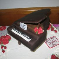"Grand Piano  i carved the piano shape from a 9"" square. the lid is fondant covered cardboard. the legs are 7"" push-in pillars painted with..."
