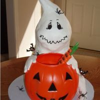 Greedy Ghost WASC cake iced in buttercream. Ghost is sitting behind trick or treat bucket holding on to it, tail of ghost comes around side. Several 8&...