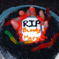 Halloween Cake Graveyard Cake with hand coming out of ground. Fingers made out of fondant with black decoration sugar.