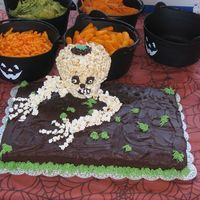 Skull Cake I did this cake for my halloween party it is chocolate cake and chocolate icing with a skull made out of popcorn and cookie crumbs for dirt...