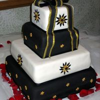 Ivory, Black And Gold Wedding Cake This is a four tier wedding cake for 200 covered with Stain Ice fondant and with all fondant accents. The gold accents were spray painted...