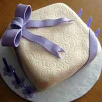 Tracy's Present Cake This was a fondant cake the I made for a friend. I used an impression mat for the scroll work.