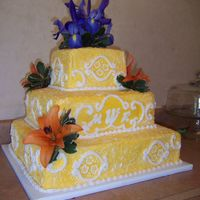 Summer Sun  Square 3-tiered white cake with lemon filling. Golden yellow buttercream stippled with white buttercream. Scrollwork and monogram finished...