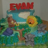 Wild Kingdom! Jungle cake for 1st birthday. BC icing with fondant animlad and name. TFirst layer was chocolate. Second layer and side layers (ponds) were...