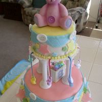 Best Baby Shower Cake Ever! Mobile utilized in tiered fondant baby shower cake with cute purple bear on top. The bottom layer is a lemon poppy seed cake and the top is...