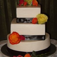 Modern Monogram Wedding Stacked buttercream cake decorated with satin ribbon and fresh flowers, and topped with a silver monogram.