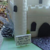 """almost Ready"" - Third View This is a closeup view of the castle cake showing a completed turret and the front yard signage from ""Knight Builders"". Thanks..."