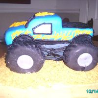 Monster Truck this cake was for a little boys 1st bday. monster truck with flames. cake and truck was yellow cake and the tires were donuts covered n mmf...