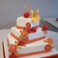 Fall Theme Wedding Cake Off center square wedding cake with fall colored gumpaste flowers.