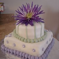 Green And Purple Birthday Cake   The flower at the top was the inspiration for this cake. I made it for my mom's birthday. It is strawberry cake with MMF.