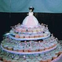 Sweet15.jpg Ok I posted this earler but this is a better pic. Quinceanera cupcake tree(300 cupcakes) with doll cake the tiara was also made of icing....