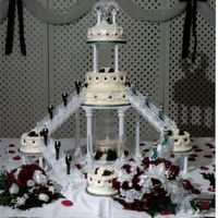 Mickey And Minnie Wedding  This is a two teir cake with three sattelite cakes. A lighted fountain resides under the first teir, giving it an elegant touch. All icing...