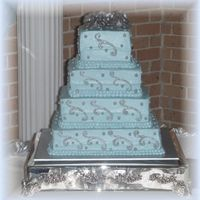 25Th Wedding Anniversary/vow Renewal Light Blue Square cakes with silver piping gel. Silver gumpaste roses used for topper. It was extremely hot here and the icing started to...