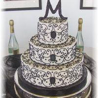 Black And White Wedding 6, 10 and 14 inch iced in buttercream with black scrollwork. Topper and center accents made with crystals.