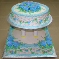 Blue And White  2-tier cake where the bottom cake is a 2kg chocolate moist cake & the top one is a 1kg vanilla buttercake. both are decorated in...