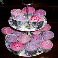 Cupcakes Pink & Purple Vanilla cupcakes in silver foil pans topped with royal icing then sprinkled with love hearts, sequins and 100's & 1,000's.