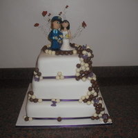 Malteser & Ivory 3 Tier Square cake, iced in Ivory with Chocolate & White Chocolate Malteser's and Marzipan Garda (Policeman) and his Bride... to...