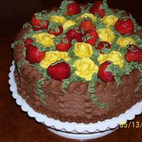 Mother's Day Cake Chocolate cake with yellow roses, and strawberries.