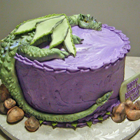 Dragon At Rest Fondant dragon and rocks. Dragon is accented with purple and green luster dust. Cake is iced with purple buttercream swirled with a bit of...