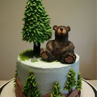 His Favorite Spot I used tip #1D to pipe the hills on the side and #352 to make the pines. Fondant is the foundation for the bear and royal icing was applied...