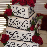 Black On White Sour cream white wedding cake torted and filled with buttercream icing. Hand piped icing scrolls. Fresh/live flowers.