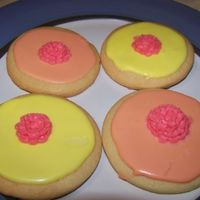 Round Decorative Sugar cookies flooded with royal icing decorated with a royal icing flower.