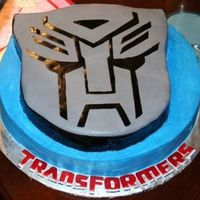 Transformers Autobot Emblem Used two cakes stacked and carved out the autobot shape on the top cake only. Blue icing is bc. Used gray fondant for emblem and painted...