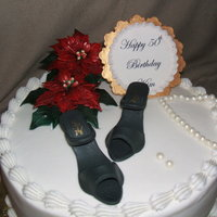 "Kim's 50Th Birthday 12"" lemon cake with blueberry filling. Iced in buttercream, gumpaste shoes, plaque and poinsettias. Chocolate clay pearls."