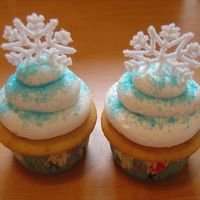 Snowflake Cupcakes  Cupcakes with buttercream frosting and royal icing snowflakes sprinkled with sugar. I made 3 dozen of these for my sons Christmas program...